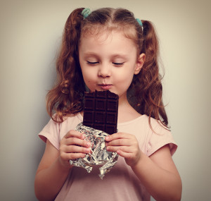 Happy kid girl eating health dark chocolate with pleasure and closed eyes. Vintage portrait